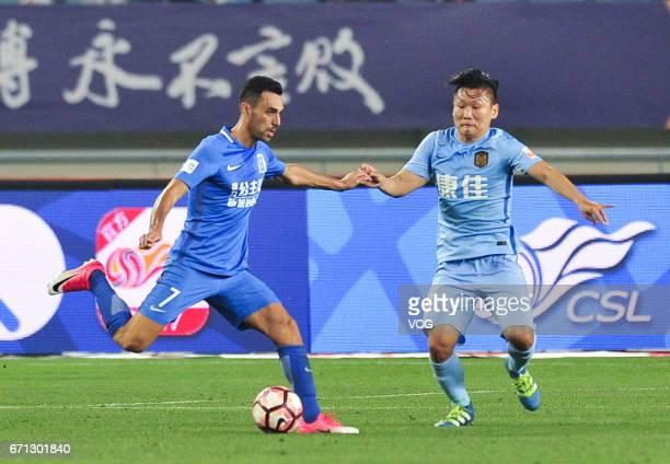 Liu Jianye of Jiangsu Suning and Eran Zahavi of Guangzhou RF compete for the ball during the 6th round match of China Super League between Jiangsu...