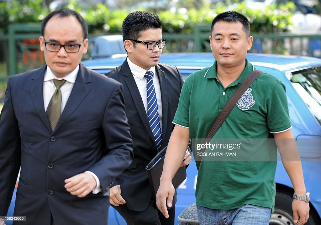Liu Xiangying (R), 33, one of four Chinese bus drivers facing possible jail for instigating Singapore's first industrial strike in 26 years, arrives at the subordinate courts with his lawyer in Singapore on December 12, 2012. Four Chinese bus drivers facing possible jail were given more time on December 12 to explore their legal options and were told to report again on December 19 for a new pre-trial conference.