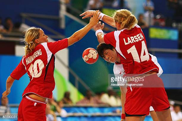Liu Xiaomei of China is tackled by Tonje Larsen and Gro Hammerseng of Norway during the handball match between Norway and China held at the Olympic...