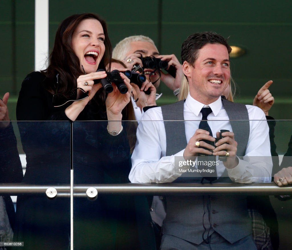Liv Tyler and Dave Gardner watch the racing as they attend day 2 'Ladies Day' of the Cheltenham Festival at Cheltenham Racecourse on March 15, 2017 in Cheltenham, England.