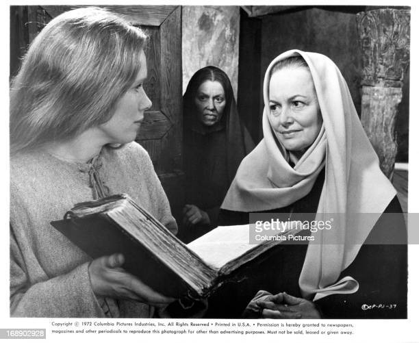 Liv Ullmann holds a book open in front of Olivia De Havilland in a scene from the film 'Pope Joan' 1972