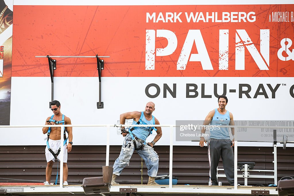 Live body builders get pumped on a billboard over Sunset Boulevard celebrating the Blu-Ray/DVD release of 'Pain & Gain' on August 26, 2013 in West Hollywood, California.