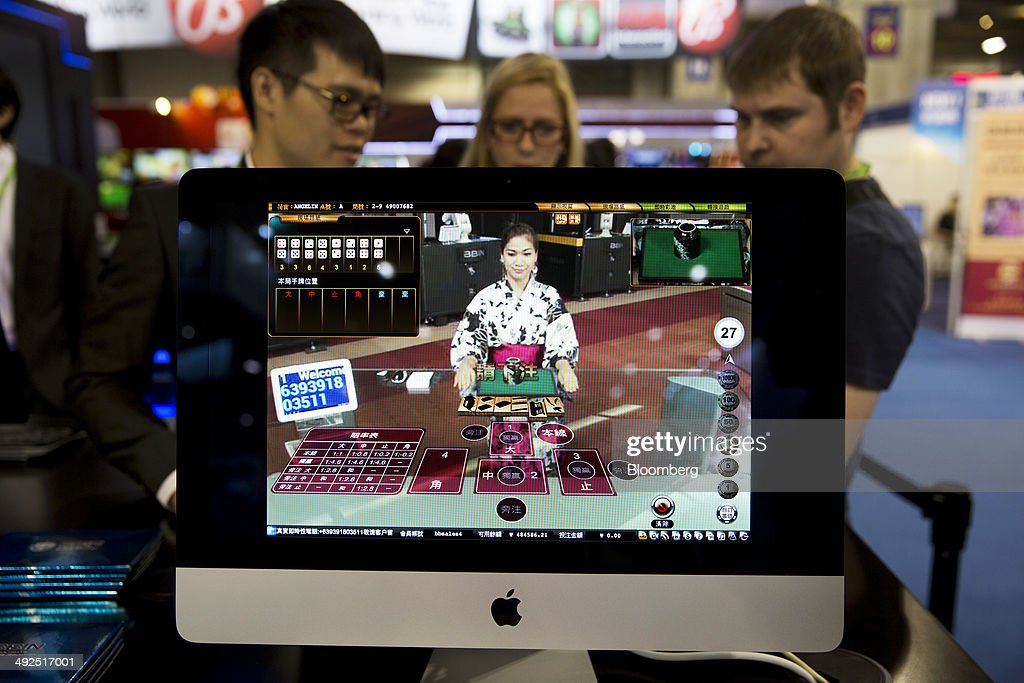 A live dealer at an online casino is displayed on an Apple Inc. iMac computer at the BBIN Technology booth at the Global Gaming Expo (G2E) inside the Venetian Macao resort and casino, operated by Sands China Ltd., a unit of Las Vegas Sands Corp., in Macau, China, on Tuesday, May 20, 2014. The gaming expo runs through May 22. Photographer: Brent Lewin/Bloomberg via Getty Images