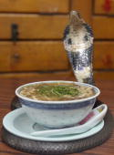 A live King Cobra is coiled around a bowl of snake soup at the Snake King Hip cafe in Kowloon Hong Kong China on Sunday July 30 2006 Snake King Hip...