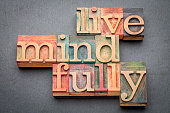 live mindfully - word abstract in letterpress wood type against gray slate stone