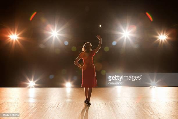 Eine Live-Perfomerin, stehend auf der Bühne mit Beleuchtung