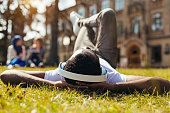Pure serenity. Sincere admirable clever guy resting after classes and lying on the grass while relaxing to the music