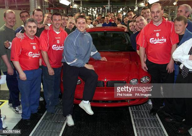 Liverpool and England footballer Michael Owen sits on a new Jaguar XType dubbed the 'baby Jag' with workers at the Jaguar Plant in Halewood on...