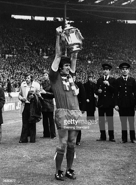 Liverpool captain Emlyn Hughes holds the FA Cup aloft in victory having beaten Newcastle United 30 in the FA Cup Final at Wembley