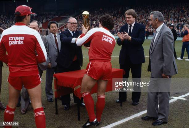 Liverpool captain Graeme Souness receives the Canon First Division Championship trophy from Football League President Jack Dunnett at Anfield prior...
