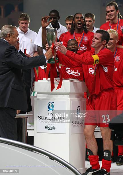 Liverpool captain Jamie Carragher is handed the trophy after his teams UEFA Super Cup victory over CSKA Moscow at the Stade Louis II in Monaco on...
