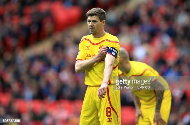 Liverpool captain Steven Gerrard adjust his armband