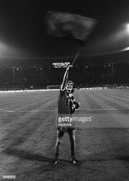 Liverpool defender Phil Thompson waves a flag in triumph after beating Bruges 10 in the final at Wembley Stadium