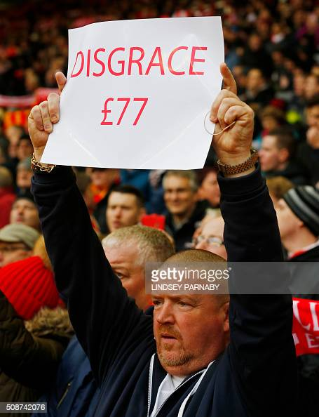 A Liverpool fan holds a banner protesting against the recently announced rise in ticket prices during the English Premier League football match...