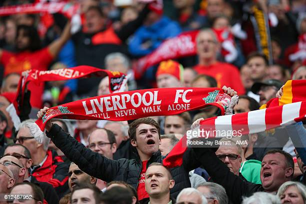 Liverpool fan holds a Liverpool scarf above his head as they sing You Will Never Walk Alone during the Premier League match between Liverpool and...