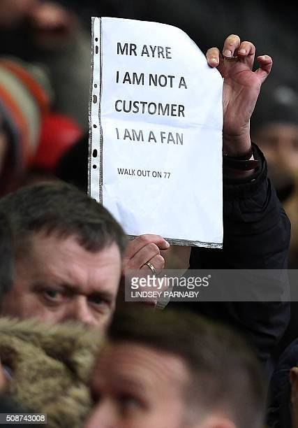 A Liverpool fan holds a poster denouncing the the announcement of a rise in ticket prices during the English Premier League football match between...