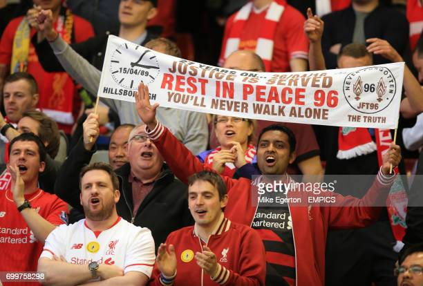 A Liverpool fan in the stands holds up a banner