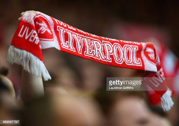 Liverpool fan raises his scarf during the Barclays Premier League match between Liverpool and Newcastle United at Anfield on May 11 2014 in Liverpool...