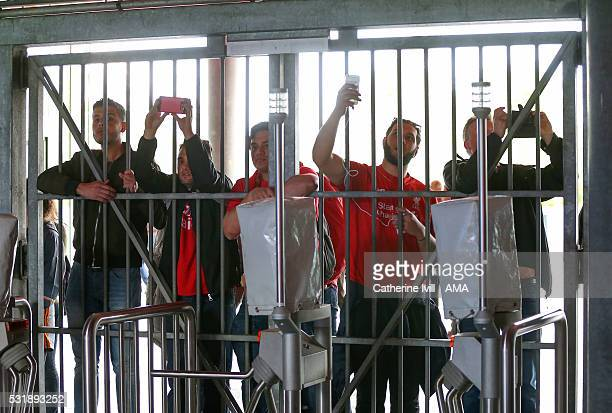 Liverpool fans peer through the gates with their phones during the training session before the UEFA Europa League Final at St JakobPark on May 17...
