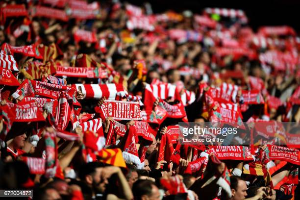 Liverpool fans raise their scarves during the Premier League match between Liverpool and Crystal Palace at Anfield on April 23 2017 in Liverpool...