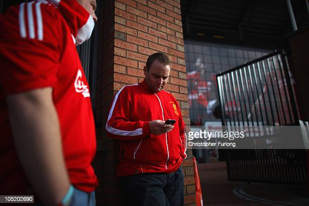 Liverpool fans stand outside Anfield and check their mobile phones for news from the high court in London on October 12 2010 in Liverpool England The...