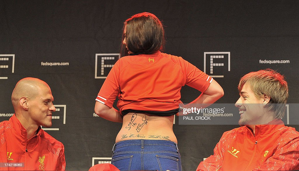 Liverpool FC defender Martin Skrtel (L) and Sebastian Coates (R) watch on as a fan shows off her signatures and her tatoo on her back during a promotional event at Federation Square in Melbourne on July 22, 2013. LIverpool FC will play the Melbourne Victory in front of a near sell-out 90,000 fans at the MCG on July 24. AFP PHOTO / Paul CROCK