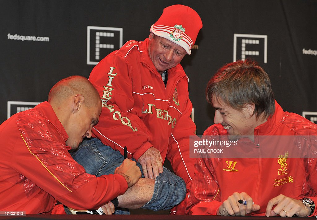 Liverpool FC defender Martin Skrtel (L) signs a fan's leg as Sebastian Coates (R) watches on during a promotional event at Federation Square in Melbourne on July 22, 2013. LIverpool FC will play the Melbourne Victory in front of a near sell-out 90,000 fans at the MCG on July 24. AFP PHOTO / Paul CROCK