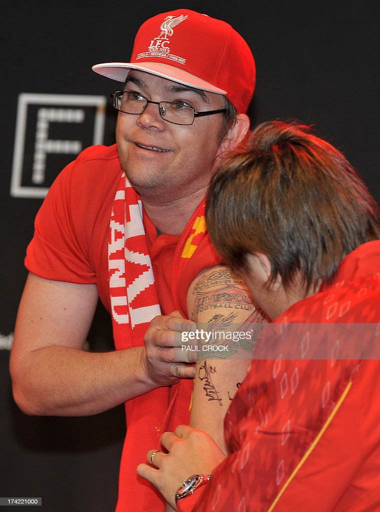Liverpool FC defender Sebastian Coates (R) signs a fan's tattooed arm during a promotional event at Federation Square in Melbourne on July 22, 2013. LIverpool FC will play the Melbourne Victory in front of a near sell-out 90,000 fans at the MCG on July 24. AFP PHOTO / Paul CROCK