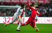 Liverpool forward Luis Suarez is brought down by Swansea defender Chico Flores during the Barclays Premier League match between Swansea City and...