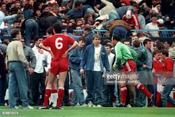 Liverpool goalkeeper Bruce Grobbelaar and Alan Hansen can only watch as the tragic events unfold around them 96 people in total lost their lives...