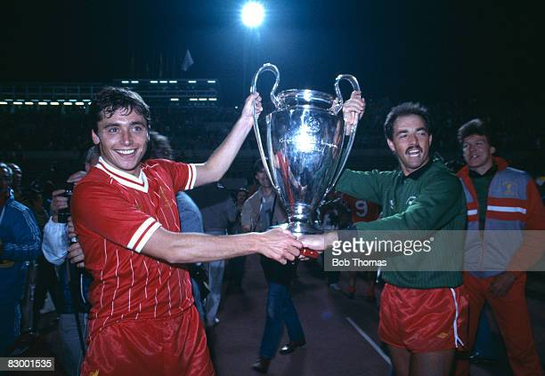Liverpool goalkeeper Bruce Grobbelaar and striker Michael Robinson carry the European Cup on the lap of honour after defeating AS Roma in the Final...