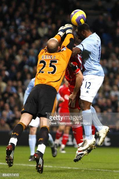 Liverpool goalkeeper Jose Reina challenges Manchester City's Darius Vassell for the ball