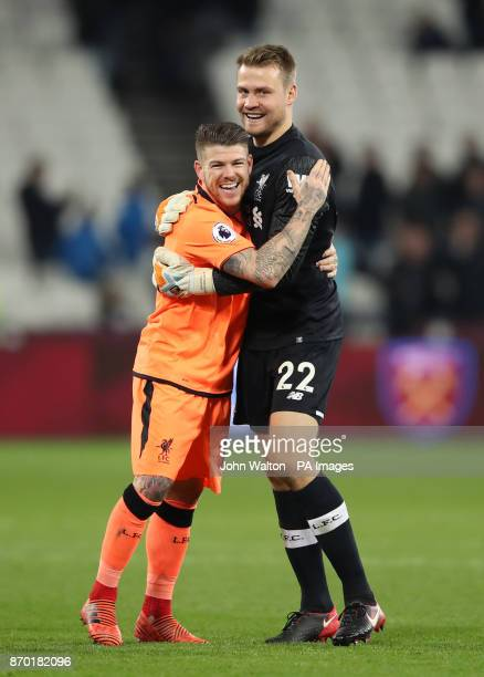Liverpool goalkeeper Simon Mignolet and Alberto Moreno celebrate victory after the Premier League match at the London Stadium