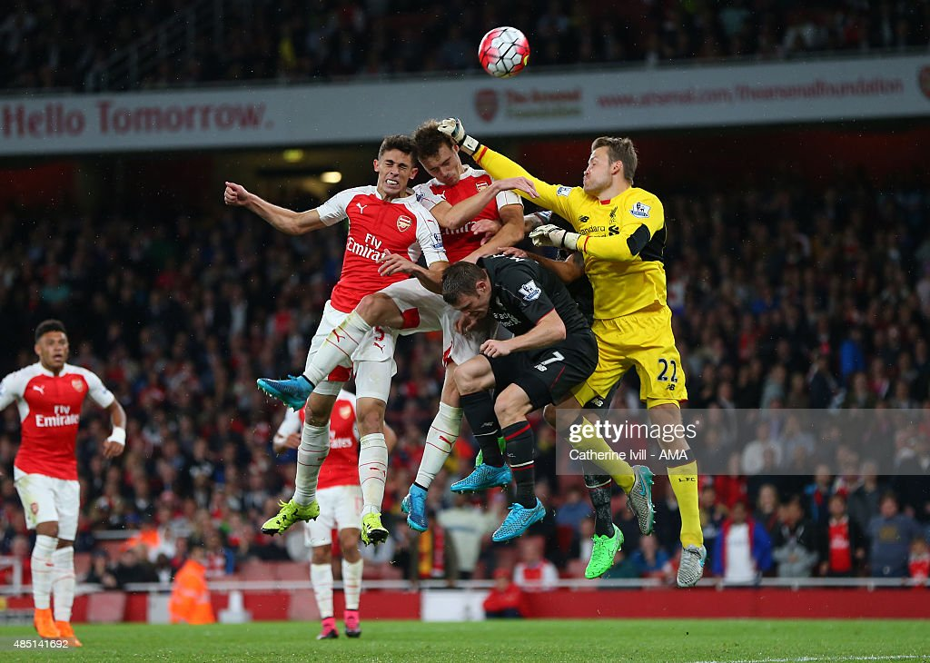 Liverpool goalkeeper Simon Mignolet punches away a last minute shot as he gets caught up with Gabriel Paulista, Calum Chambers of Arsenal and James Milner of Liverpool during the Barclays Premier League match between Arsenal and Liverpool at the Emirates Stadium on August 24, 2015 in London, United Kingdom.