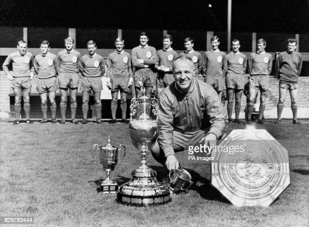Liverpool manager Bill Shankly crouches by the trophies that his team won the previous season including the League Championship trophy and the FA...