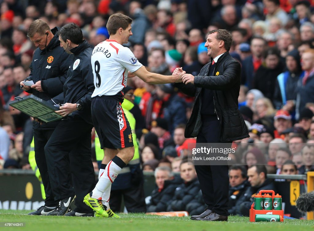 Liverpool manager Brendan Rodgers greets <a gi-track='captionPersonalityLinkClicked' href=/galleries/search?phrase=Steven+Gerrard&family=editorial&specificpeople=202052 ng-click='$event.stopPropagation()'>Steven Gerrard</a> of Liverpool with a smile after substituting him late on during the Barclays Premier League match between Manchester United and Liverpool at Old Trafford on March 16, 2014 in Manchester, England.