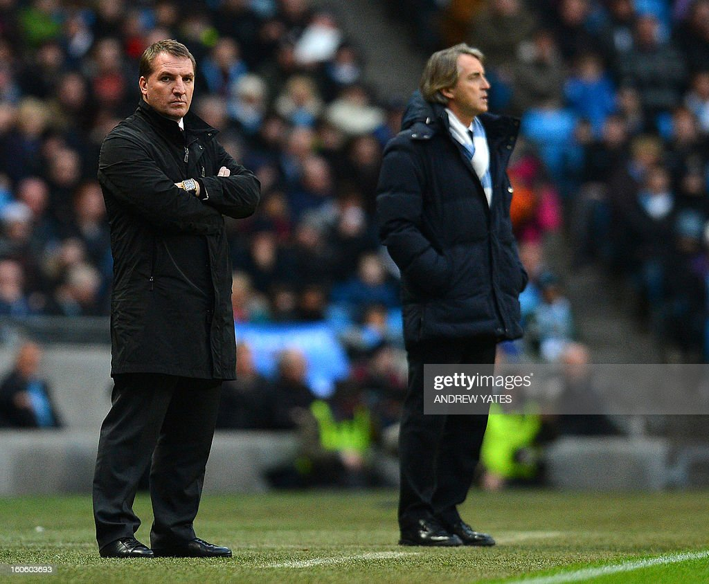 "Liverpool manager Brendan Rodgers (L) looks on during the English Premier League football match between Manchester City and Liverpool at The Etihad stadium in Manchester, north-west England, on February 3, 2013. The game finished 2-2. AFP PHOTO/ANDREW YATES == RESTRICTED TO EDITORIAL USE. No use with unauthorized audio, video, data, fixture lists, club/league logos or ""live"" services. Online in-match use limited to 45 images, no video emulation. No use in betting, games or single club/league/player publications =="