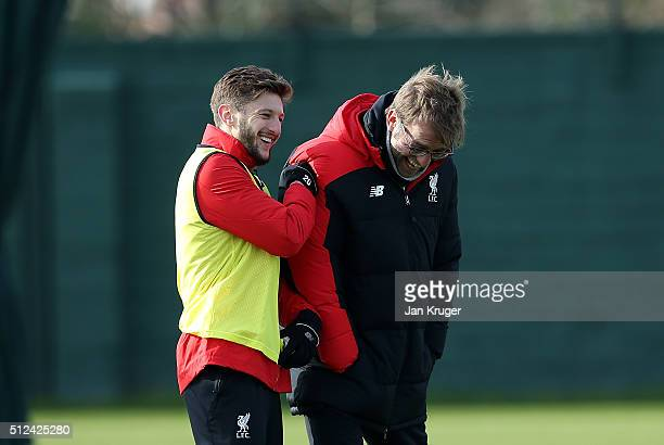 Liverpool manager Jurgen Klopp shares a joke with Adam Lallana during a training session ahead of their Capital One Cup final match against...