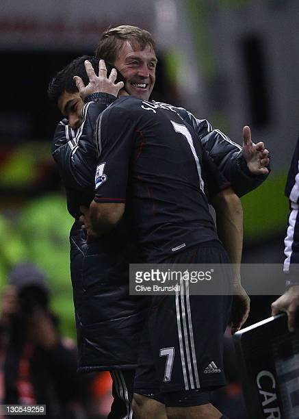 Liverpool manager Kenny Dalglish congratulates his double goal scorer Luis Suarez after substituting him near thew end of the match during the...