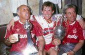 Liverpool manager Kenny Dalglish with coach Ronnie Moran and assistant manager Roy Evans celebrate winning the league title with the trophy in the...