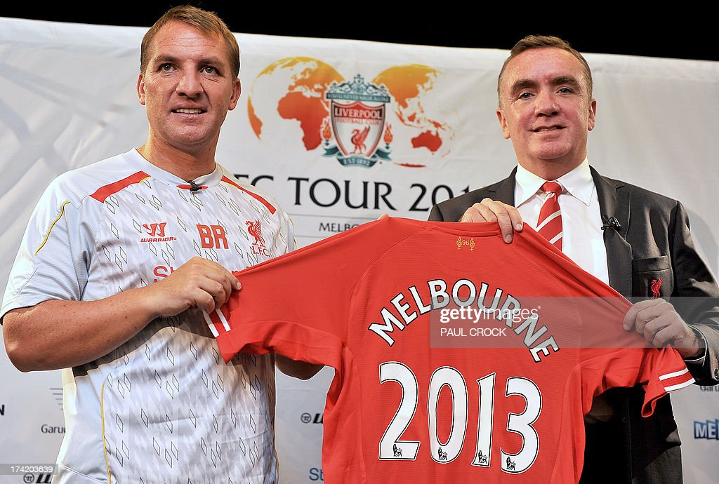 Liverpool Managing Director Ian Ayre (R) and team manager Brendan Rogers (L) hold up the team's tour jersey during a press conference in Melbourne on July 22, 2013. Rodgers said on July 22 he expects unsettled star Luis Suarez to stay with the club after the Uruguay striker arrived in Australia to join his teammates in 'great spirits'. AFP PHOTO / Paul CROCK