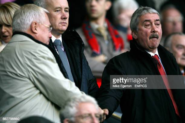 Liverpool owner George Gillett shakes hands with chairman David Moores watched by chief executive Rick Parry