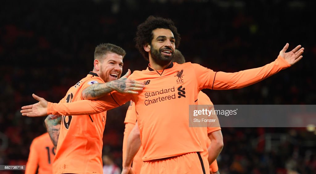 Liverpool player Mohamed Salah celebrates his second goal with Alberto Moreno (l) during the Premier League match between Stoke City and Liverpool at Bet365 Stadium on November 29, 2017 in Stoke on Trent, England.