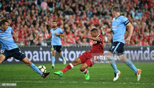 Liverpool player Rhian Brewster shoots on goal as Sydney FC players Sebastian Ryall and Alex Wilkinson look on during their endofseason friendly...