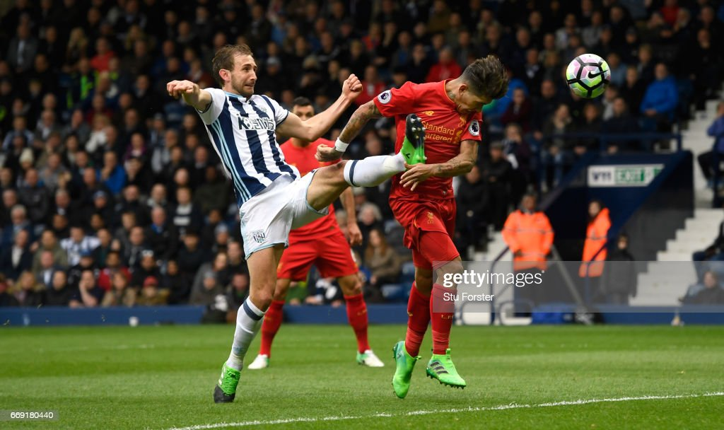 Liverpool player Roberto Firmino scores the first goal with a header despite the challenge of West Brom defender Craig Dawson during the Premier League match between West Bromwich Albion and Liverpool at The Hawthorns on April 16, 2017 in West Bromwich, England.