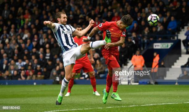 Liverpool player Roberto Firmino scores the first goal with a header despite the challenge of West Brom defender Craig Dawson during the Premier...