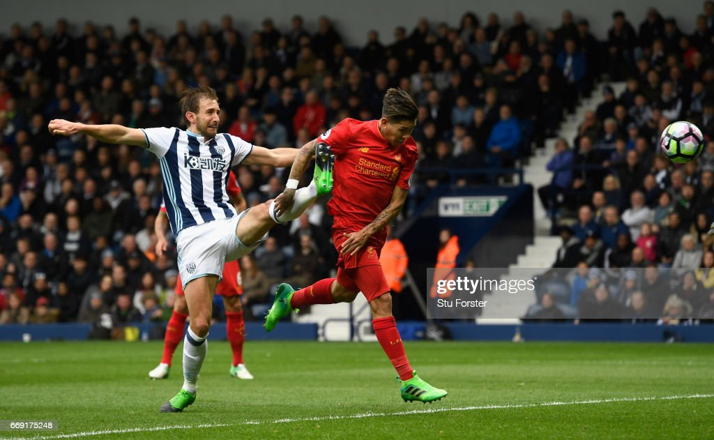 Liverpool player Roberto Firmino scores the firstr goal with a header despite the challenge of West Brom defender Gareth McAuley during the Premier League match between West Bromwich Albion and Liverpool at The Hawthorns on April 16, 2017 in West Bromwich, England.