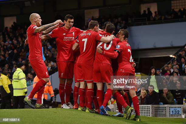 Liverpool players celebrate their team's first goal scored by Eliaquim Mangala of Manchester City during the Barclays Premier League match between...