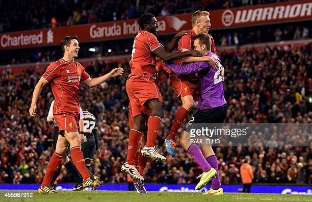 Liverpool players celebrate with Belgian goalkeeper Simon Mignolet after their 1413 penalty shoot out victory in the English League Cup third round...