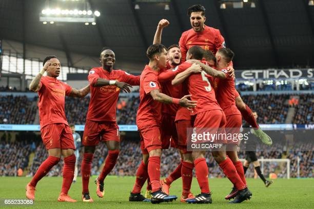 Liverpool players celebrate with Liverpool's English midfielder James Milner after he opens the scoring from the penalty spot during the English...